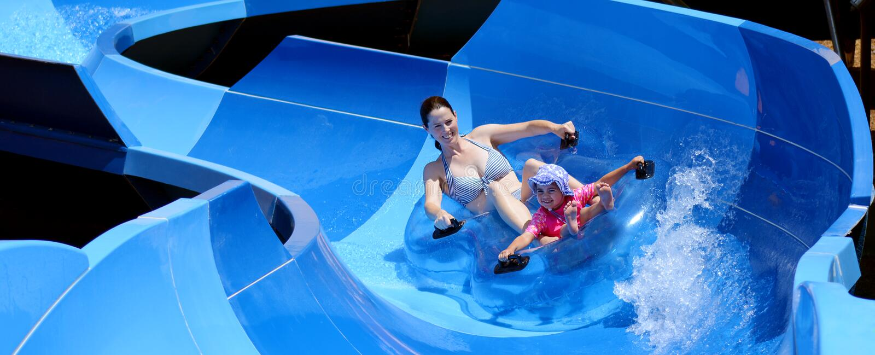 Madre y niño que se divierten en parque del agua fotos de archivo