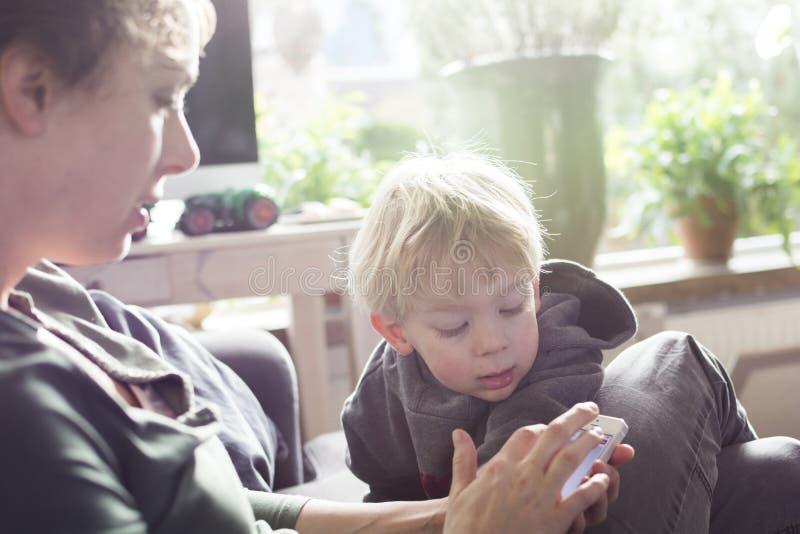 Madre y niño que usa smartphone imagenes de archivo