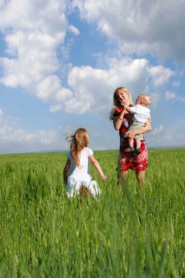 Madre y niños en campo verde fotografía de archivo