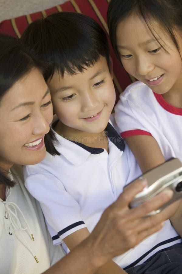 Madre y niños en el sofá que mira imágenes en cierre de la cámara digital para arriba foto de archivo