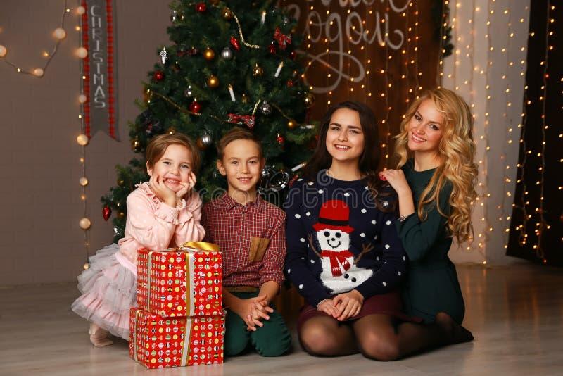Madre y niños felices de la familia en la Navidad en el árbol de navidad con los regalos fotografía de archivo libre de regalías
