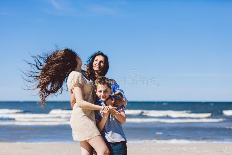 Madre y niños que abrazan en la playa imágenes de archivo libres de regalías