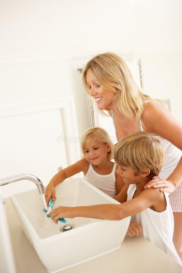 Madre y niños que aplican los dientes con brocha en cuarto de baño foto de archivo