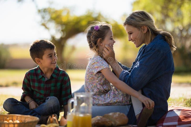 Madre y niños que gozan junto en comida campestre en parque fotos de archivo