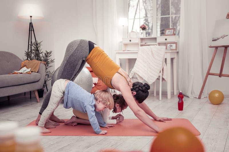 Madre y niños que hacen ejercicios de la yoga cada mañana juntos fotografía de archivo