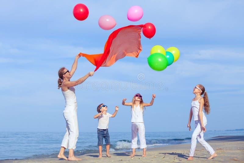 Madre y niños que juegan en la playa en el tiempo del día imagen de archivo