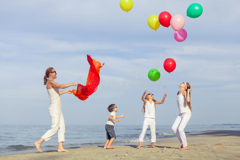 Madre y niños que juegan en la playa en el tiempo del día foto de archivo