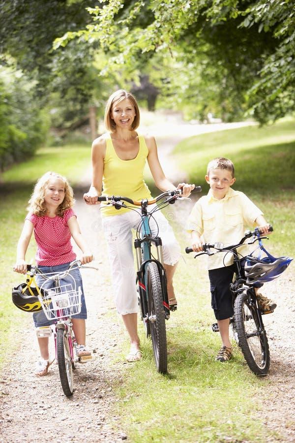 Madre y niños que montan las bicis en campo imágenes de archivo libres de regalías