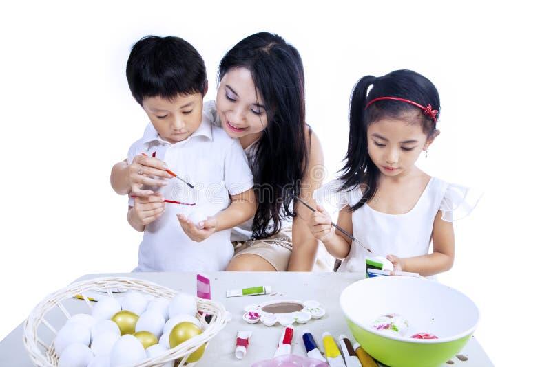 Madre y niños que pintan los huevos de Pascua imágenes de archivo libres de regalías