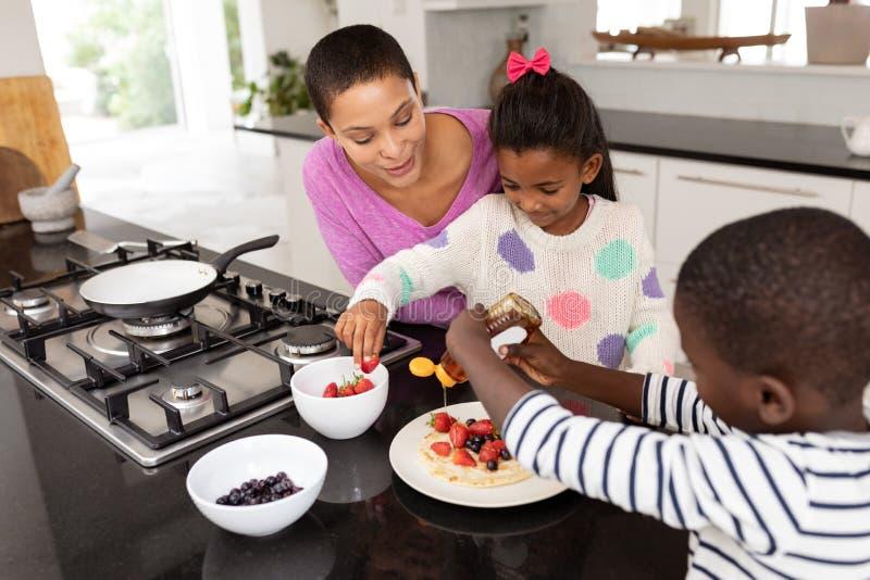 Madre y niños que preparan la comida en un worktop en cocina imagen de archivo libre de regalías