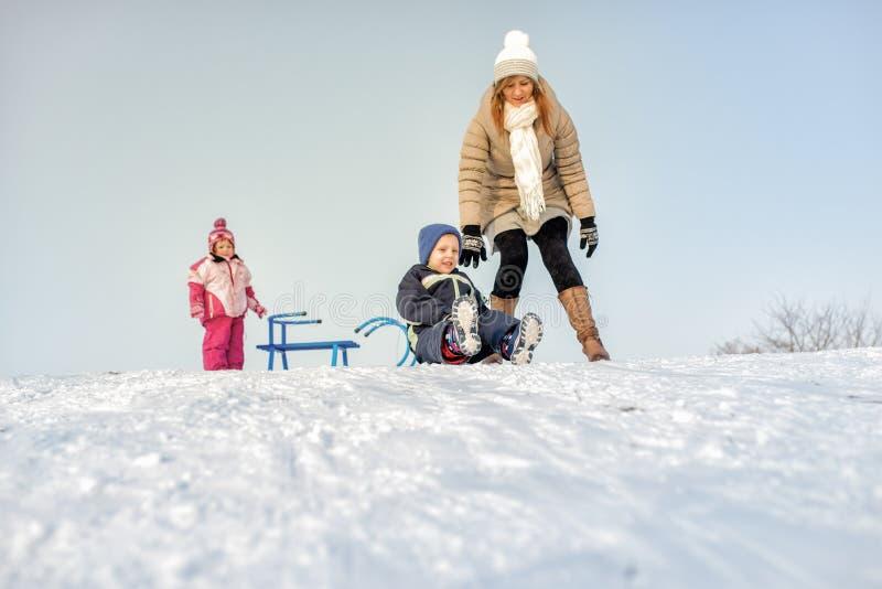 Madre y niños que se divierten en nieve fotos de archivo libres de regalías