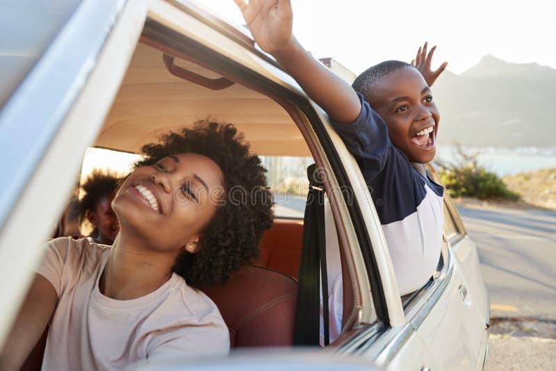 Madre y niños que se relajan en coche durante viaje por carretera fotografía de archivo