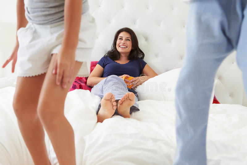 Madre y niños que se relajan en pijamas que llevan de la cama foto de archivo