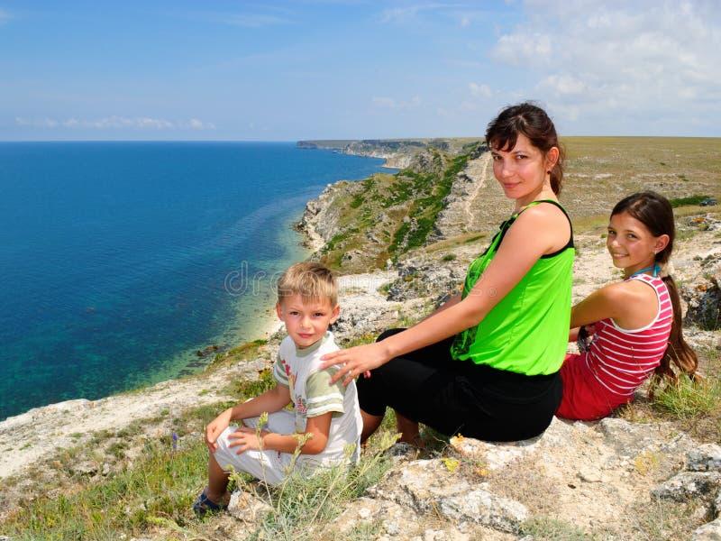 Madre y niños que se sientan en el borde fotos de archivo