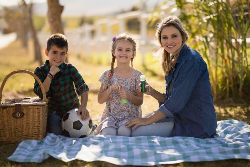 Madre y niños sonrientes que se sientan junto en parque foto de archivo libre de regalías