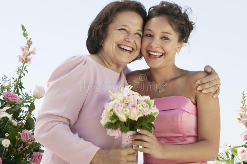 Madre y novia con el ramo al aire libre (retrato) imagen de archivo libre de regalías