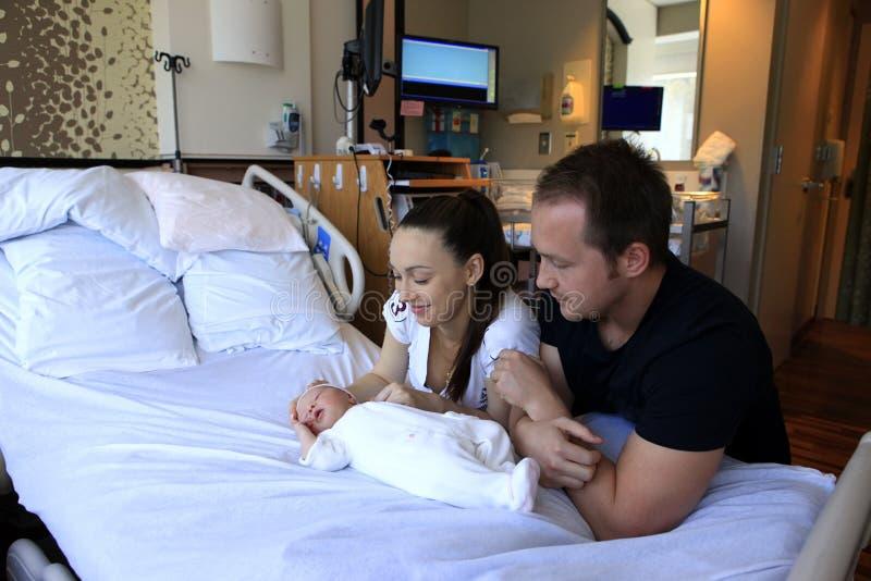 Madre y padre con su hija recién nacida fotografía de archivo