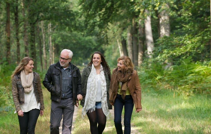 Madre y padre que disfrutan de un paseo a través del bosque con las hijas foto de archivo libre de regalías