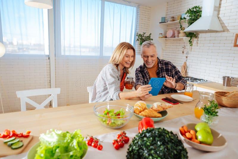 Madre y padre que tienen charla video con la hija en la mañana fotografía de archivo