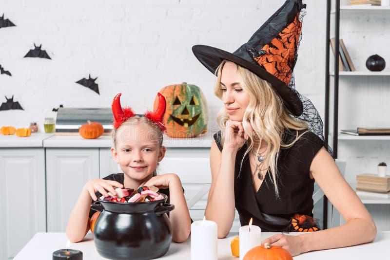 madre y pequeña hija en disfraces de Halloween en la tabla con las invitaciones en pote negro imagen de archivo