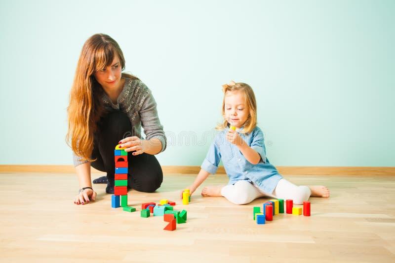 Madre y pequeño edificio de la hija de bloques de madera fotografía de archivo