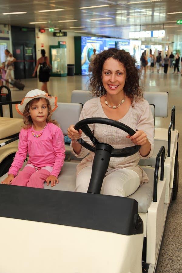 Madre y pequeño montar a caballo de la hija en el coche eléctrico