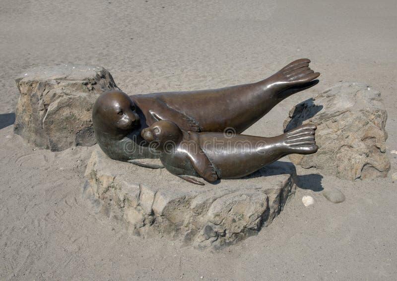 Madre y perrito, Alki Beach, Seattle, Washington del puerto-sello de la escultura de bronce imagenes de archivo