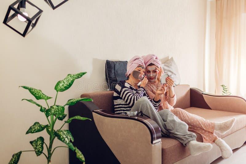 Madre y su hija adulta que aplican las máscaras faciales que miran el espejo Mujeres que se enfrían y que se relajan en casa fotos de archivo libres de regalías