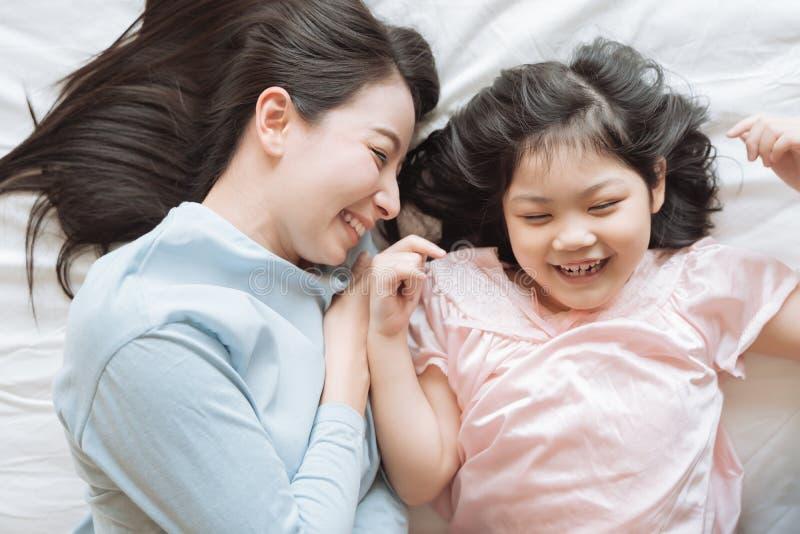 Madre y su muchacha del niño de la hija que abrazan a su mamá en el dormitorio Familia asi?tica feliz fotos de archivo libres de regalías