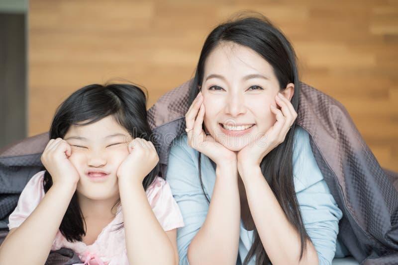 Madre y su muchacha del niño de la hija que juegan en el dormitorio y que ponen la manta Familia asi?tica feliz fotos de archivo libres de regalías