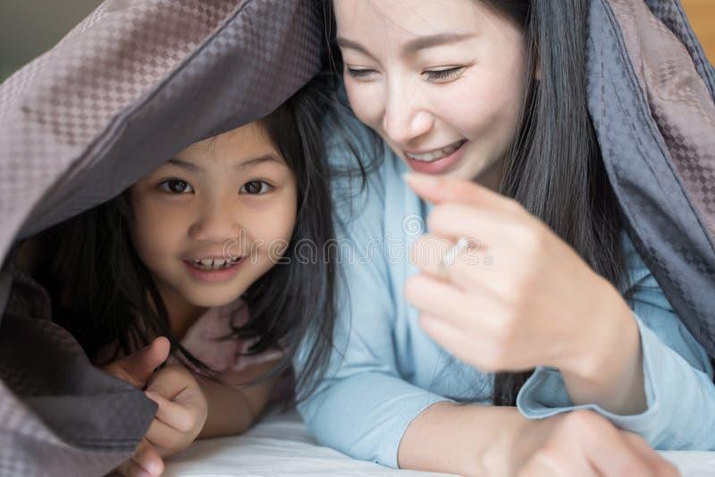 Madre y su muchacha del niño de la hija que juegan en el dormitorio y que ponen la manta Familia asi?tica feliz imágenes de archivo libres de regalías