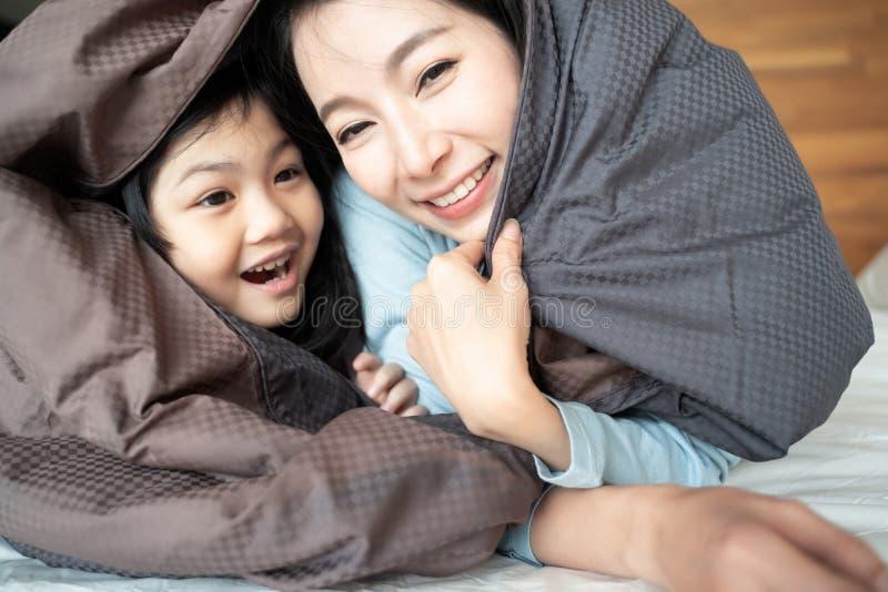 Madre y su muchacha del niño de la hija que juegan en el dormitorio y que ponen la manta Familia asi?tica feliz fotografía de archivo