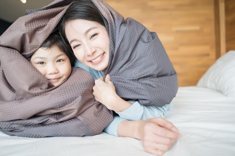 Madre y su muchacha del niño de la hija que juegan en el dormitorio y que ponen la manta Familia asi?tica feliz fotografía de archivo libre de regalías