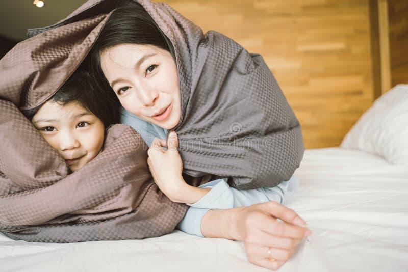 Madre y su muchacha del niño de la hija que juegan en el dormitorio y que ponen la manta Familia asi?tica feliz foto de archivo