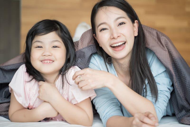 Madre y su muchacha del niño de la hija que juegan en el dormitorio y que ponen la manta Familia asi?tica feliz imagenes de archivo