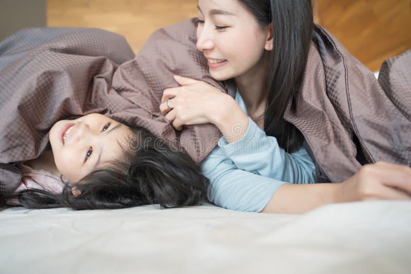 Madre y su muchacha del niño de la hija que juegan en el dormitorio y que ponen la manta Familia asi?tica feliz foto de archivo libre de regalías