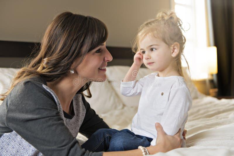 Madre y su muchacha del niño de la hija que tardan buen tiempo en cama imagen de archivo libre de regalías