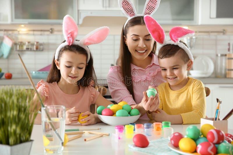 Madre y sus niños con las vendas de los oídos del conejito que pintan los huevos de Pascua fotos de archivo libres de regalías