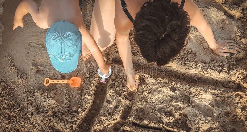 Madre y un niño que se divierte en la playa Mire de arriba imagen de archivo