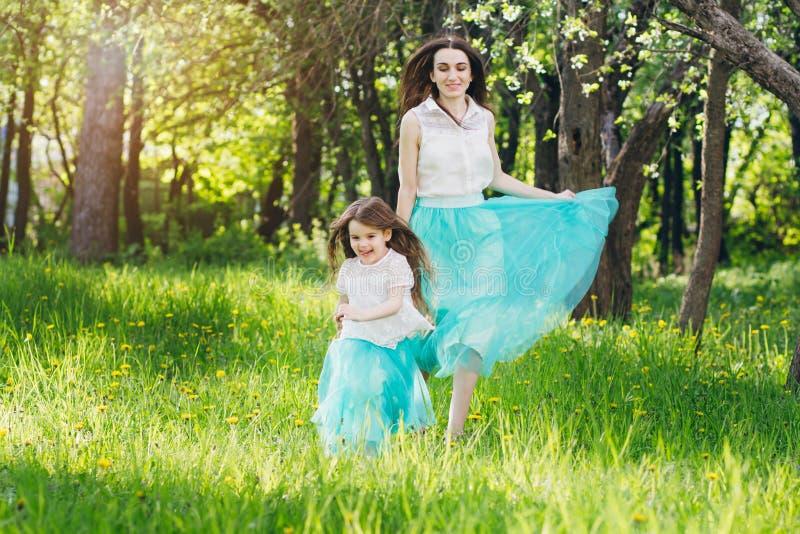 Madre y un pequeño paseo de la hija en la primavera Apple floreciente imagenes de archivo