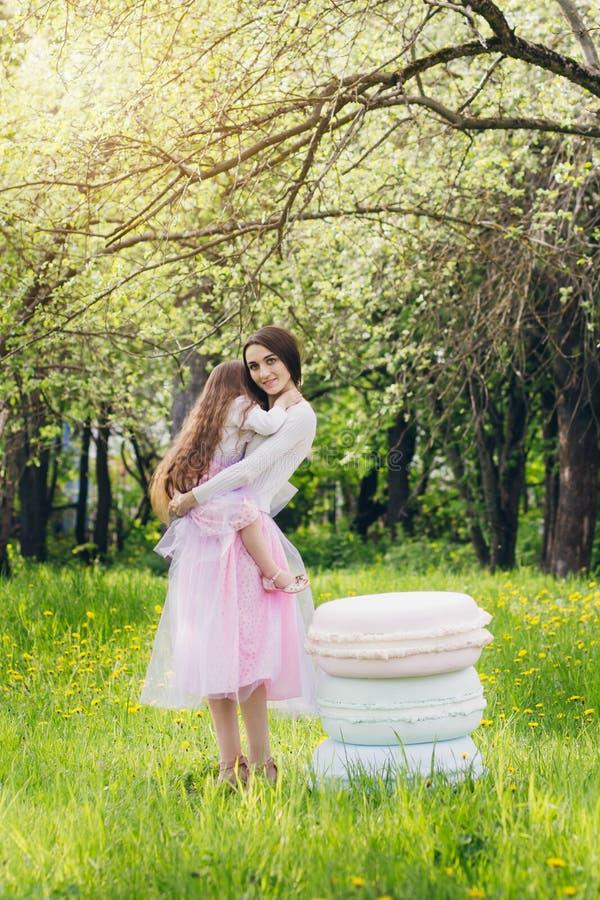 Madre y un pequeño paseo de la hija en la primavera Apple floreciente foto de archivo libre de regalías