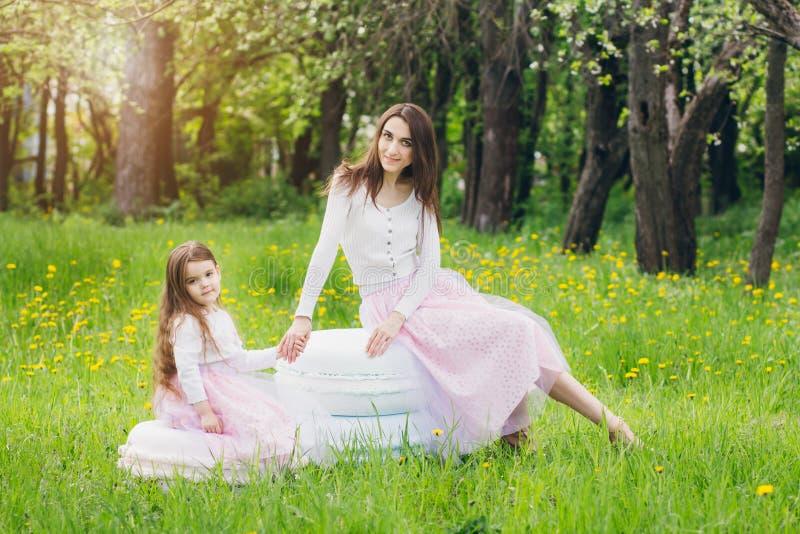 Madre y un pequeño paseo de la hija en la primavera Apple floreciente imagen de archivo libre de regalías