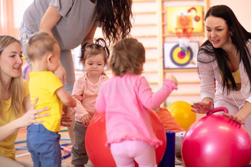 Madres con los niños felices que hacen ejercicios con la bola gimnástica roja en el gimnasio Concepto de cuidar para la salud del imagenes de archivo