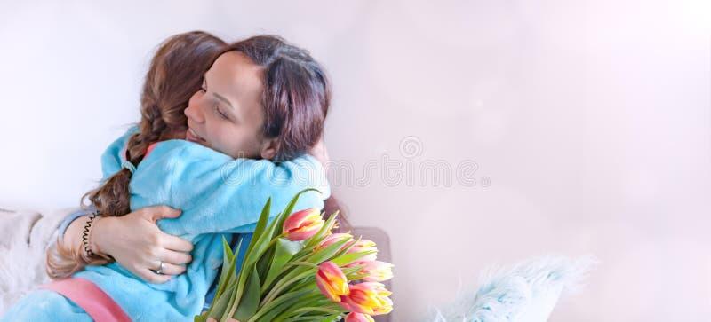 Madres e hijas apacibles de los abrazos, enhorabuena en el d?a de fiesta y flores Concepto de la tarjeta de felicitaci?n del d?a  imagen de archivo libre de regalías