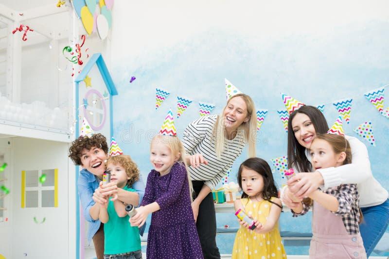 Madres extáticas y niños que estallan las galletas imagenes de archivo