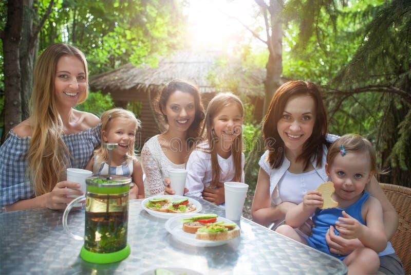 Madres felices y sus pequeñas hijas adorables en el café del aire libre imagenes de archivo
