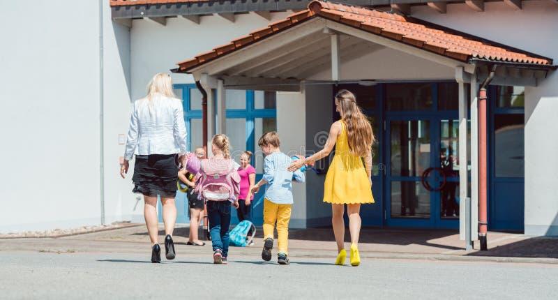Madres que traen a los niños a la escuela por la mañana fotografía de archivo