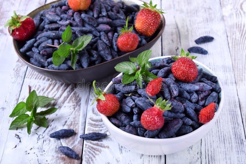 Madreselvas y fresas frescas en los cuencos rematados con la menta foto de archivo libre de regalías