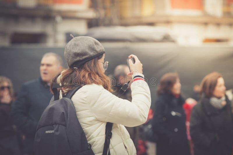 Madri, Espanha - 12 de fevereiro de 2018: Um turista novo toma fotos no prefeito da plaza, Madri foto de stock royalty free