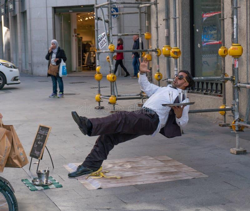 Madri, Espanha - novembro 11,2017: Ato não identificado do executor da rua como é um garçom que desliza em uma casca da banana pe foto de stock royalty free